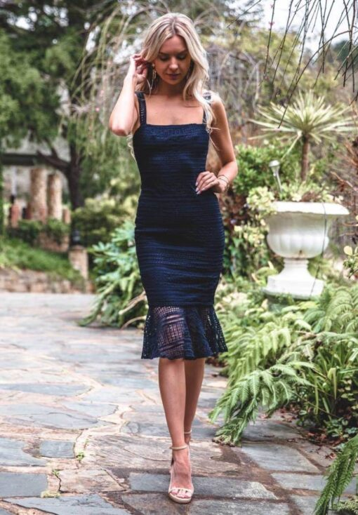 The Poppy Dress is a figure contouring mid-length dress featuring an intricate lace overlay & sheer fishtail hem & box neckline